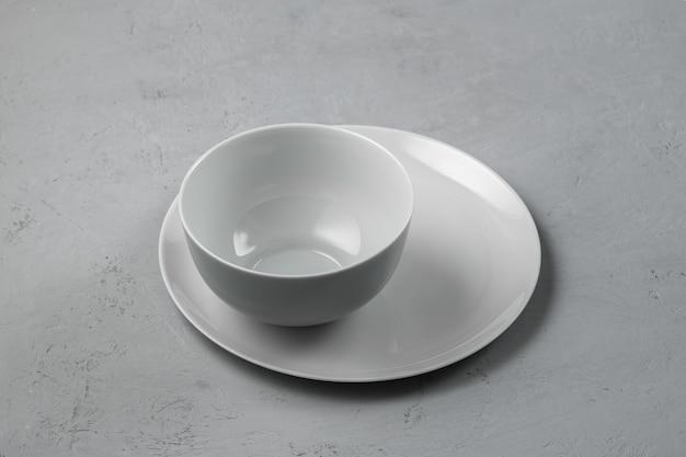 Tigela com um prato em um fundo cinza de concreto