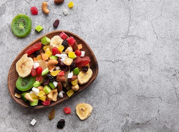 Tigela com várias frutas secas e nozes em um fundo cinza de concreto