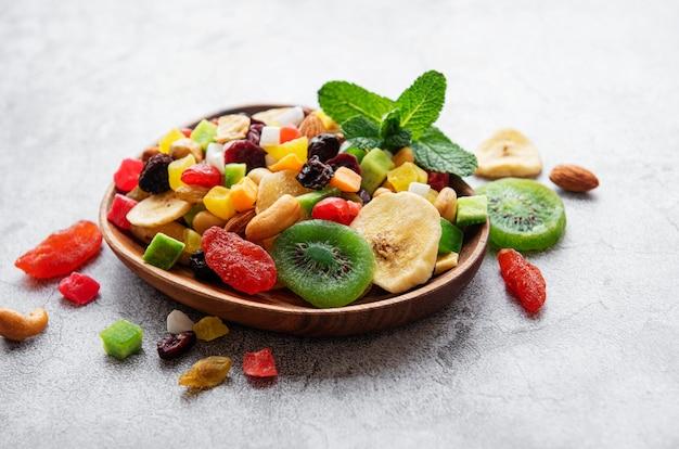 Tigela com várias frutas secas e nozes em uma mesa de concreto cinza