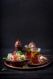 Tigela com vários pedaços de manjar turco lokum e chá preto com hortelã em uma mesa escura