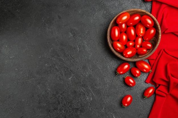Tigela com vista inferior com toalha vermelha de tomate cereja e tomate cereja em fundo escuro