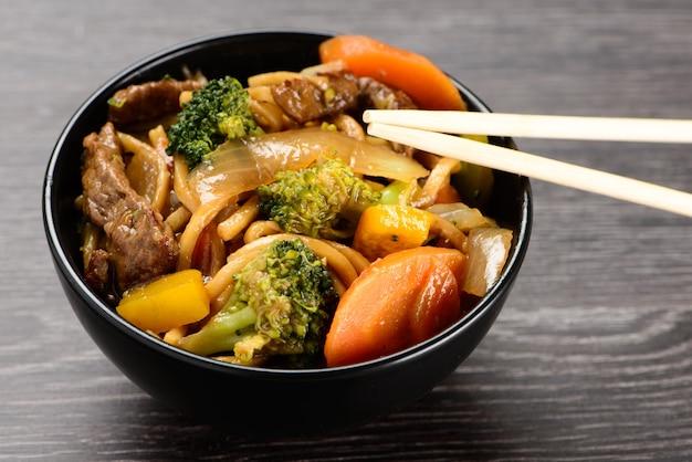 Tigela com yakisoba e hashi em fundo preto