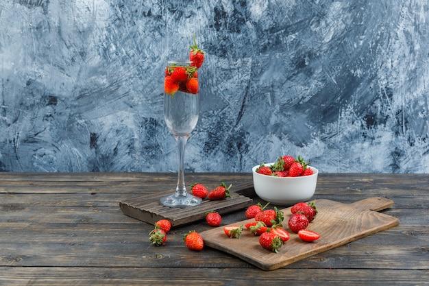 Tigela, copo e tábua de cortar com morangos