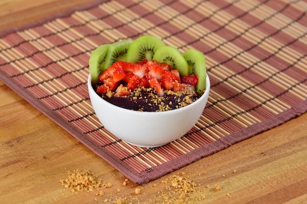 Tigela de açaí brasileiro com amendoim, kiwi, morango e açaí cremoso em um guardanapo de mesa de bambu