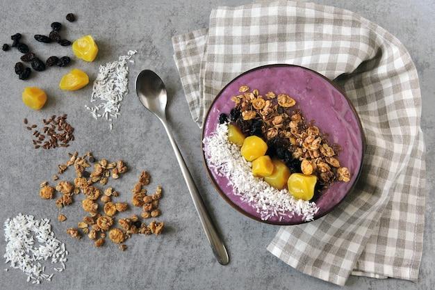 Tigela de açaí colorido brilhante com granola e frutos secos.