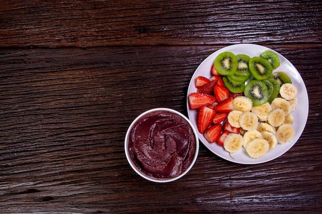 Tigela de açaí com frutas, morango, banana e kiwi em madeira escura