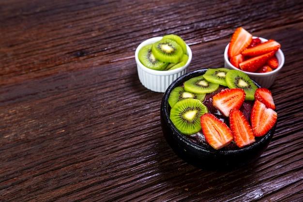 Tigela de açaí com frutas, morango e kiwi em madeira escura