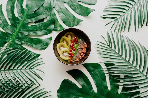 Tigela de açaí com frutas saudáveis, kiwi, abacate na folha de palmeira tropical. comida vegetariana saudável.