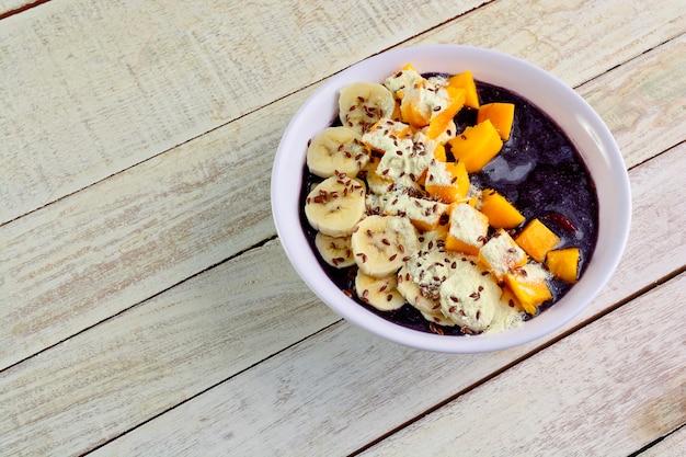 Tigela de açaí com manga, banana, granola, semente de linho e leite condensado em mesa de madeira branca