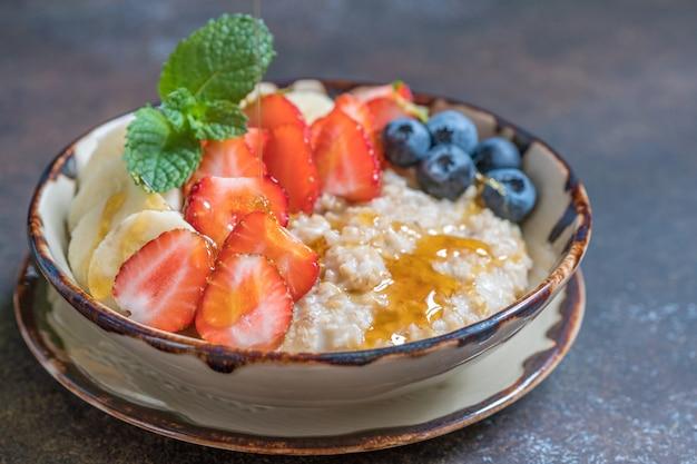 Tigela de aço delicioso corte aveia com frutas frescas, mel