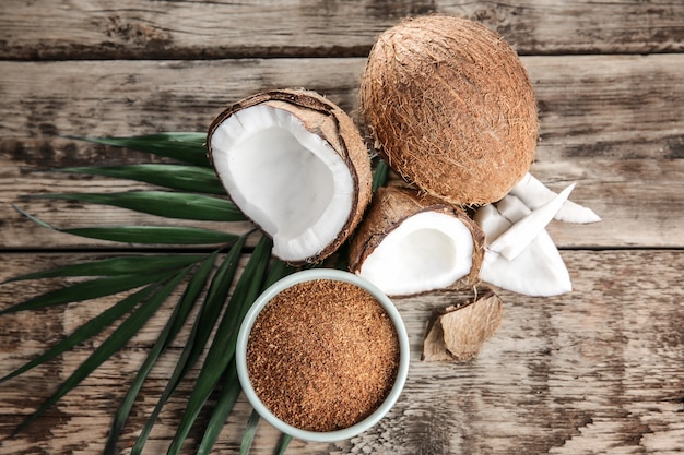 Tigela de açúcar mascavo e coco na mesa de madeira