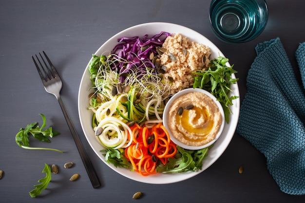Tigela de almoço de cuscuz vegetariano com cenoura em espiral e abobrinha, hummus e repolho roxo
