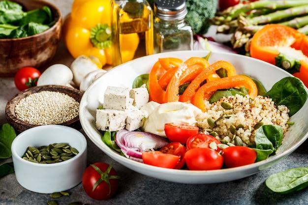 Tigela de almoço vegan com quinoa, brócolis, homus e cogumelos.