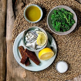 Tigela de anchovas em conserva ou filé de sardinha em azeite servido com azeite de limão e sal tostado