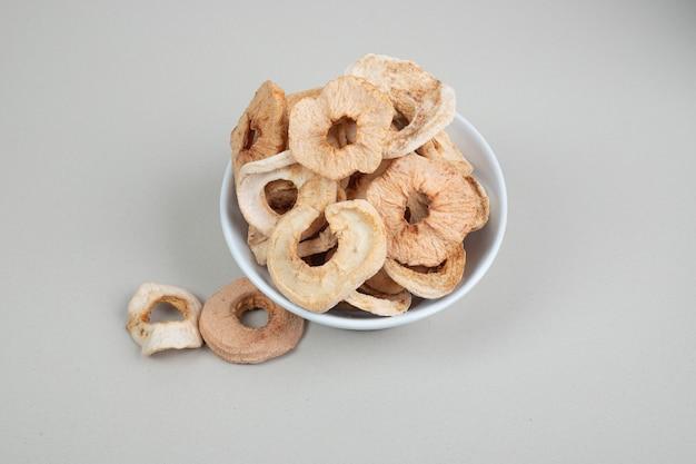 Tigela de anéis de maçã seca na superfície branca