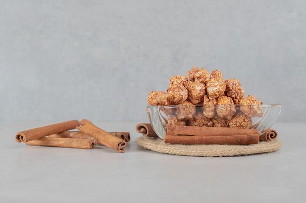 Tigela de aperitivo ao lado de um feixe de cortes de canela na mesa de mármore.