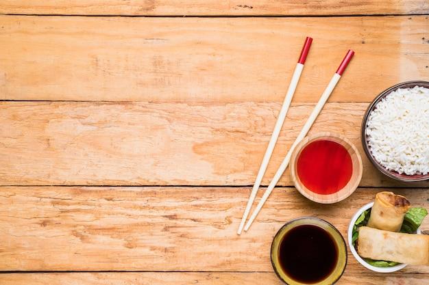 Tigela de arroz branco; rolinhos primavera e molhos com pauzinhos na mesa de madeira