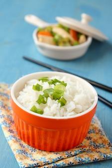 Tigela de arroz cozido com cebola verde