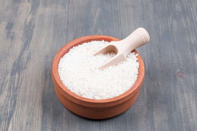 Tigela de arroz cozido com colher na mesa de madeira