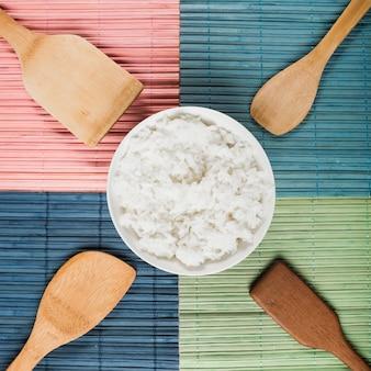 Tigela de arroz cozido no vapor com diferentes tipos de espátula de madeira no colorido placemat