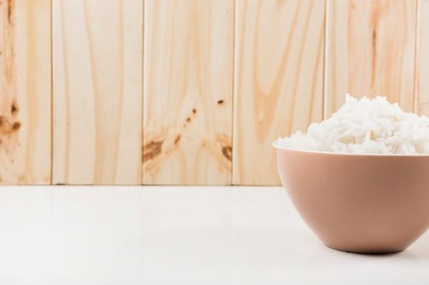 Tigela de arroz cozido no vapor na mesa branca contra a parede de madeira