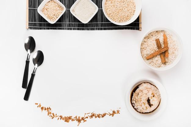 Tigela de arroz cru com colher e arroz de molho de soja no fundo branco