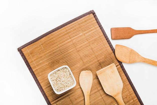 Tigela de arroz cru plana e espátulas de madeira em placemat sobre fundo branco