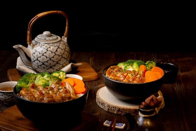 Tigela de arroz de frango teriyaki grill em estilo de comida asiática com fundo de bule de chá