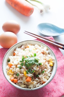 Tigela de arroz frito, cenoura e ovo em tecido rosa, colher, pauzinhos e ingredientes para o fundo