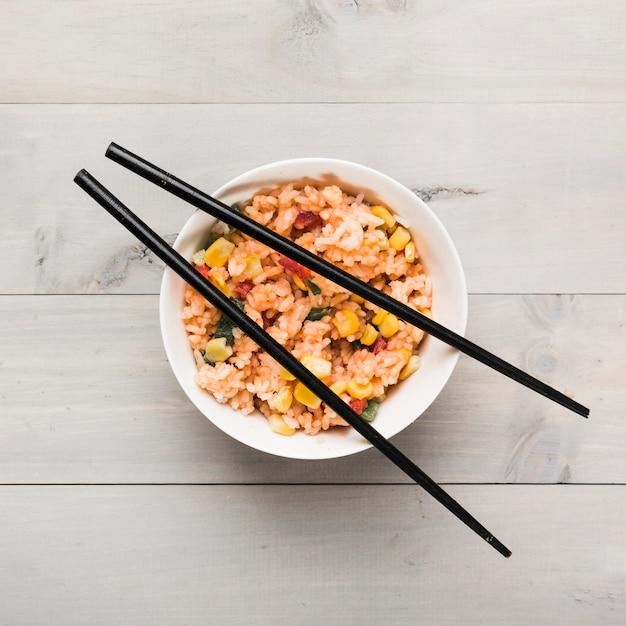 Tigela de arroz frito chinês com pauzinhos pretos na mesa de madeira