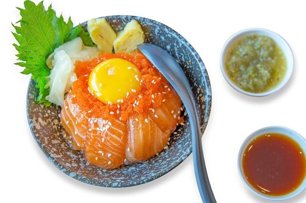 Tigela de arroz japonês com sashimi fatiado de salmão ovos cozidos, ovas de camarão com molho de frutos do mar, foco seletivo