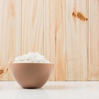 Tigela de arroz no chão em frente a parede de madeira