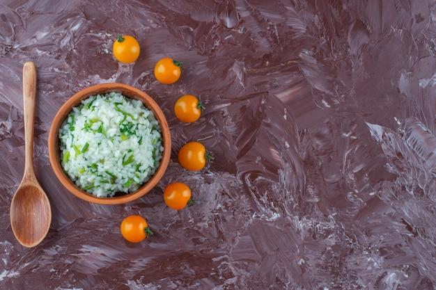 Tigela de arroz, pequenos tomates e colher na superfície de mármore