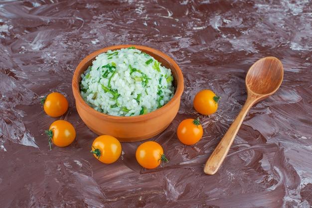 Tigela de arroz, tomate e colher, no fundo de mármore.