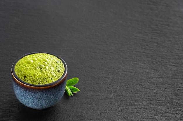 Tigela de azul com chá verde matcha, ao lado de folhas de chá