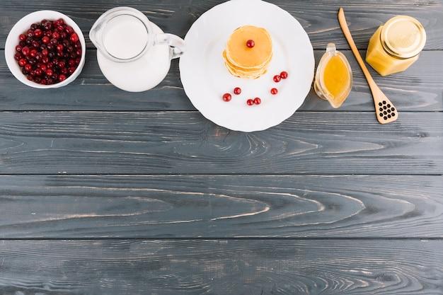 Tigela de bagas de groselhas vermelhas; leite; mel e panquecas no pano de fundo texturizado de madeira