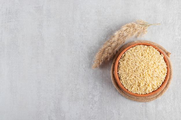 Tigela de barro cheia de arroz cru colocado no fundo de pedra.