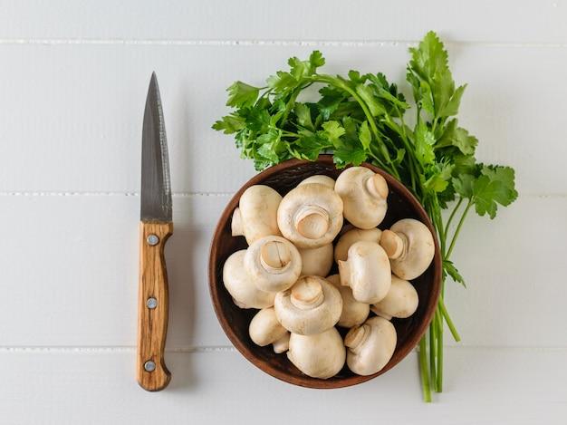 Tigela de barro com cogumelos e salsa em uma mesa de madeira branca
