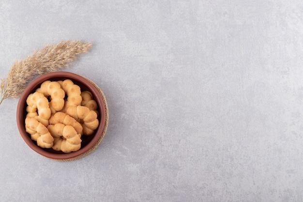 Tigela de barro com flores em forma de biscoitos doces na mesa de pedra.
