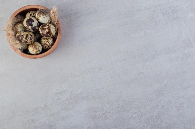 Tigela de barro com ovos de codorna crus na mesa de pedra.