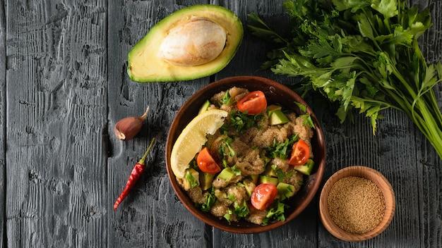 Tigela de barro com salada de sementes de amaranto com abacate, limão, tomate e salsa e tigela com azeite de oliva em uma mesa de preto escuro. a vista do topo.