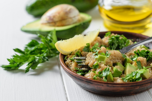 Tigela de barro com salada de sementes de amaranto com fatias de abacate, limão e salsa na mesa de madeira branca.