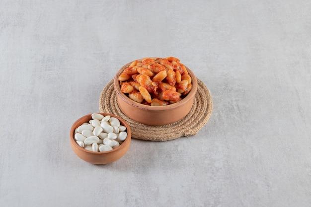 Tigela de barro de grãos de soja cozidos e feijão cru em fundo de pedra.