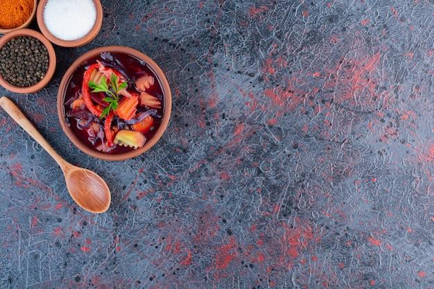 Tigela de barro de sopa de legumes fresca com condimentos na superfície de mármore.