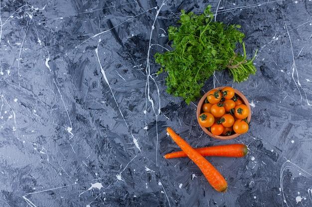 Tigela de barro de tomate cereja com folhas de salsa e cenoura em fundo azul.