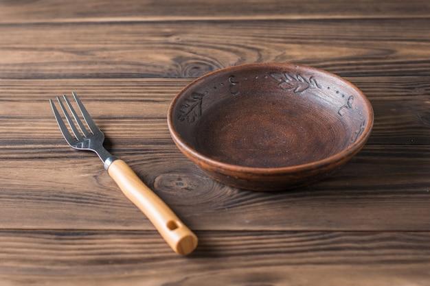 Tigela de barro em uma mesa de madeira marrom. cerâmica para a cozinha.