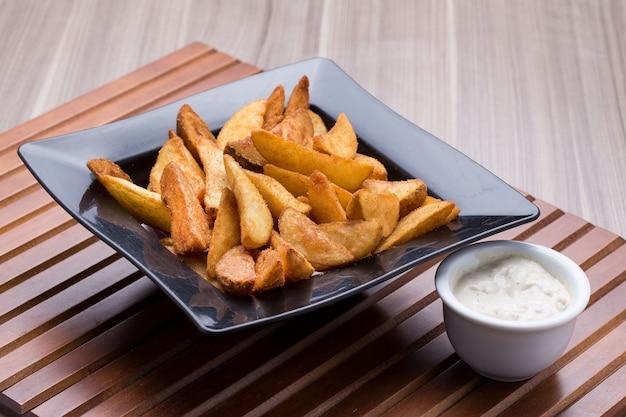 Tigela de batatas fritas da vila e uma tigela pequena de molho em uma mesa de madeira