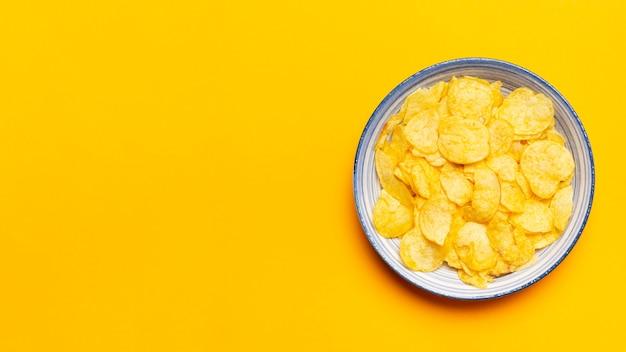 Tigela de batatas fritas de vista superior em fundo amarelo
