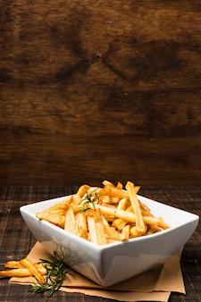 Tigela de batatas fritas na mesa de madeira