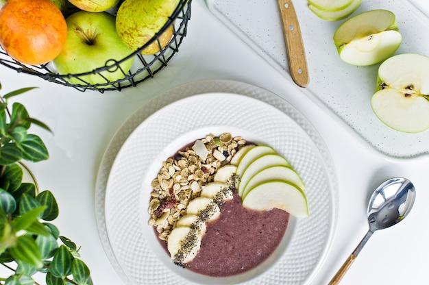Tigela de batido com banana, maçã, sementes de chia, aveia e iogurte.